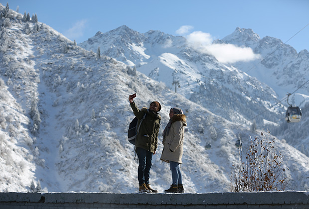 Tourist take a selfie with the backdrop of Tien Shan mountains after a recent snowfall in Almaty, Kazakhstan November 13, 2018. REUTERS/Pavel Mikheyev