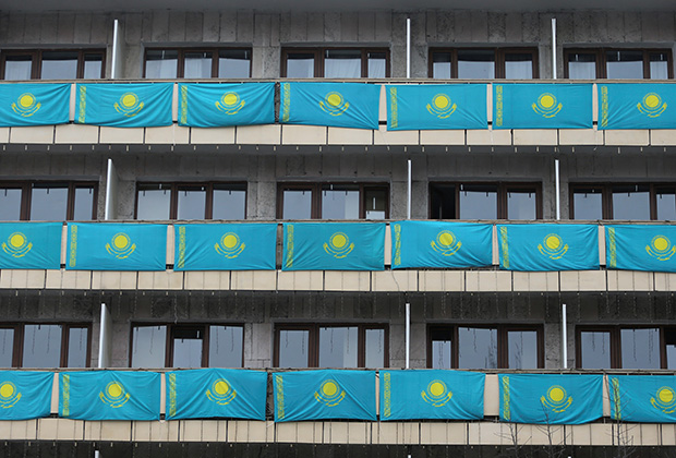 Kazakh state flags hang out from balconies of a building on Independence Day in Almaty, Kazakhstan December 16, 2020. REUTERS/Pavel Mikheyev