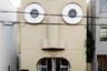 """Дом с изображением лица на фасаде для графического дизайнера в 1974 году придумал японский архитектор Кадзумаса Ямасита (Kazumasa Yamashita). Он <a href=""""https://www.architectural-review.com/archive/face-house-in-kyoto-japan-by-kazumasa-yamashita"""" target=""""_blank"""">построил</a> в городе Киото прямоугольную конструкцию из железобетона и с помощью стекла и декора «очеловечил» постройку: окна сделаны в виде глаз, двери— в виде рта. Наибольшую трудность у создателя вызвал нос: Ямасита реализовал его при помощи трех колонн, изображающих переносицу и ноздри. Внутри двухэтажного дома умещаются кухня, гостиная, совмещенная со столовой, ванная комната, спальни и рабочие зоны."""