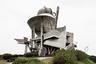 """В 1995 году японский архитектор Такасаки Масахару (Takasaki Masaharu) <a href=""""https://architizer.com/projects/kihoku-astronomical-museum/"""" target=""""_blank"""">решил вдохнуть</a> новую жизнь в пенсионерский город Каноя, небо которого считается самым красивым в Японии. Масахару привлек внимание к месту, построив на высоте 550 метров над уровнем моря здание астрономического музея Кихоку. Оно представляет собой переплетение конструкций разных форм и размеров: от колонн до массивных многогранников. Благодаря удачной локации из музея открывается вид на вулкан Сакурадзима. В качестве основного материала архитектор использовал бетон, а некоторые участки покрыл стальными панелями. Проект Масахару получился удачным: появление музея широко обсуждали в прессе, а у местных жителей появился повод для гордости."""