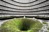 """Интересная постройка находится в бельгийском городе Шарлеруа. С 1921 года она служила электростанцией IM и на протяжении десятилетий обеспечивала район энергией. Однако в 2007 году экологи <a href=""""https://www.atlasobscura.com/places/power-plant-im"""" target=""""_blank"""">добились</a> ее закрытия из-за больших выбросов углекислого газа. Вскоре электростанция превратилась в место паломничества туристов: наибольший интерес вызывает охладительная установка — градирня, покрывшаяся со временем растительностью. Помещение напоминает место съемок фантастического фильма, и почти каждый посетитель стремится запечатлеть себя на фоне уходящей вглубь дыры. Несмотря на популярность объекта, власти города планируют его снести — они уже опечатали вход и демонтировали лестницу, по которой можно было забраться внутрь."""