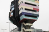 """Брутальное здание с ярким фасадом в стиле поп-арт с 1976 года украшает берлинский район Штеглиц и <a href=""""https://www.atlasobscura.com/places/the-bierpinsel-berlin-germany"""" target=""""_blank"""">возвышается</a> над городом на 47 метров. Необычная конструкция получила название Bierpinsel, что переводится как «пивная щетка». Задумка принадлежит архитектору Ральфу Шулеру (Ralf Schüler) и его жене Урсулине Шулер-Витте (Ursulina Schüler-Witte) — во время работы супруги вдохновлялись образом дерева и формой его кроны. Изначально в Bierpinsel располагался ресторан, позже внутри открылись ночной клуб и кафе. Однако заведения не приносили большой прибыли владельцам и приводили к банкротству. С 2006 года постройка пустует. Новый владелец <a href=""""http://architectuul.com/architecture/bierpinsel"""" target=""""_blank"""">предложил</a> изменить концепцию и выкрасить объект в золотой цвет, однако в городе не оценили идею и выступили за сохранение оригинального дизайна."""