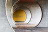 """В первой половине 1990-х годов швейцарский архитектор Марио Ботта (Mario Botta) решил изменить представление людей о жилье и <a href=""""http://www.botta.ch/en/SPAZI DELL-ABITARE?idx=6"""" target=""""_blank"""">придумал</a> комплекс из ста апартаментов в коммуне Новаццано. Особенность строений — четкая геометрия. Ботта использовал в основном прямоугольные формы, но добавил и изгибы. Части соединены крытой галереей с проходами в виде круглых арок. Они <a href=""""https://elephant.art/iotd/mario-botta-novazzano-housing-complex-switzerland-1992/"""" target=""""_blank"""">образуют</a> гипнотическое пространство тоннеля с идеальной симметрией и ярким акцентом в виде стены, выкрашенной  охрой. Для фасада здания Ботта выбрал лососевый и голубой тона. Кроме жилых помещений в комплексе есть просторный двор и небольшой торговый центр."""