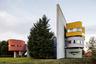 """Проект Wall House в 1970-х годах задумал американский архитектор Джон Хейдук (John Hejduk) и планировал реализовать его в штате Коннектикут. Однако полет фантазии автора оказался слишком дорогим для заказчика, и строительство отложили. В 2001 году, через год после смерти Хейдука, постройка появилась в нидерландском городе Гронингене. Особенность дома — массивная стена высотой 18,5 метра. Она разделяет дом на две части и <a href=""""http://architectuul.com/architecture/wall-house-2"""" target=""""_blank"""">символизирует</a> четкие границы между рабочей и домашней зонами. Внутри <a href=""""https://www.archdaily.com/205541/ad-classics-wall-house-2-john-hejduk"""" target=""""_blank"""">находятся</a> спальня, кухня, столовая, гостиная и кабинет. Сегодня Wall House 2 <a href=""""https://www.groningermuseum.nl/museum/wallhouse-2"""" target=""""_blank"""">служит</a> музеем, где проводят выставки и другие мероприятия."""