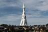 """Белая бетонная башня украшает пейзаж японского города Тондабаяси. Полая внутри конструкция была создана в 1970 году японским архитектурным бюро Nikken Sekkei. Ее высота— 180 метров, и благодаря заостренной вершине башня <a href=""""https://archive.is/h5zfi#selection-551.0-551.241"""" target=""""_blank"""">выглядит</a> как устремленный в небо палец. Постройка задумывалась как Великая молитвенная башня и должна напоминать о жертвах военных конфликтов, независимо от их вероисповедания, расы, места рождения и убеждений. Она символизирует стремление людей к миру и призывает не допускать убийств. Ходили слухи, что реализовать проект предлагали художнику Пабло Пикассо, однако он отказался от идеи из-за сложности конструкции. С течением времени башня стала неотъемлемой частью города — местные жители говорят, что моментально чувствуют себя как дома, когда видят ее из иллюминатора самолета."""