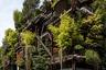 """В 2012 году архитектор Лучано Пиа (Luciano Pia) решил пересмотреть типичные представления о жилых домах и в буквальном смысле добавить им больше кислорода: в Турине он спроектировал здание площадью 7,5 тысячи квадратных метров на 63 квартир, покрытое деревьями. Для реализации проекта Пиа выбрал черепицу из лиственницы, а в качестве опорной конструкции использовал стальные колонны, сделанные в форме стволов деревьев. Пустоты заполнили разнообразные растения, которые <a href=""""https://www.archdaily.com/609260/25-green-luciano-pia"""" target=""""_blank"""">создали</a> внутри особый микроклимат. Жильцы получили возможность, сидя дома, наслаждаться зеленым пейзажем — окна некоторых квартир <a href=""""https://www.designboom.com/architecture/luciano-pia-25-verde-treehouse-torino-italy-03-13-2015/"""" target=""""_blank"""">выходят</a> во двор, засаженный деревьями, и имеют выход на крышу. С помощью цветочных горшков архитектору фактически <a href=""""https://www.hauteresidence.com/luciano-pia-25-verde-turin-italy/"""" target=""""_blank"""">удалось создать</a> оазис среди бетонных блоков."""