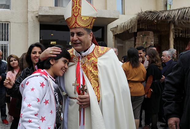 Священник обнимает девочку-христианку после мессы в Багдаде