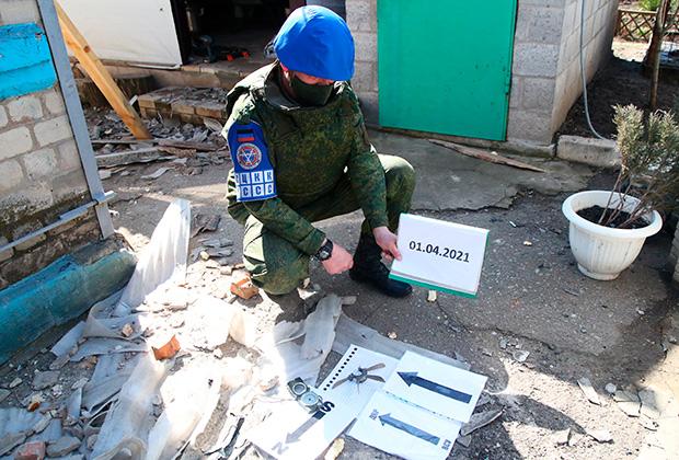 Представитель ДНР в Совместном центре контроля и координации фиксирует фрагменты снаряда, найденные на месте обстрела частного жилого дома в поселке Александровка