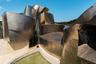 """В 1997 году Гери реализовал один из своих самых амбициозных проектов — музей современного искусства в Бильбао. Здание считается испанским филиалом нью-йоркского музея, который носит имя мецената Соломона Гуггенхайма. Расположенная на берегу реки Нервьон постройка сложной формы быстро превратилась в яркую достопримечательность, изменив облик города и традиционное представление людей о музеях — произошедшее даже стали <a href=""""https://www.archdaily.com/422470/ad-classics-the-guggenheim-museum-bilbao-frank-gehry"""" target=""""_blank"""">называть</a> «эффектом Бильбао». Под впечатлением от работы Гери <a href=""""https://www.nytimes.com/2007/09/23/travel/23bilbao.html?ei=5087&em&en=898bb5be11939f56&ex=1190606400"""" target=""""_blank"""">остался</a> и известный деятель архитектуры Филип Джонсон (Philip Johnson) — он считал ее «величайшим зданием нашего времени».<br><br>Положительную оценку музей площадью 24 тысячи квадратных метров получил благодаря необычной конструкции. Фасад здания состоит из массивных панелей, переплетенных друг с другом. Конструкция требовала серьезных математических расчетов — для получения точных показателей <a href=""""https://www.archdaily.com/422470/ad-classics-the-guggenheim-museum-bilbao-frank-gehry"""" target=""""_blank"""">использовали</a> специальное программное обеспечение CATIA.<br><br>Во время работы Гери <a href=""""https://www.youtube.com/watch?v=XrVCVJOcvzs"""" target=""""_blank"""">вдохновлялся</a> образом складок ткани — панели должны имитировать движение струящегося материала. Архитектор считал, что сложная конструкция создаст ощущение теплоты и любви, а плавные линии сделают ее «живой». В качестве главного материала использовали титан. Изначально Гери выбрал сталь, но вскоре увидел, как на титановую пластину попадают капли дождя, и она приобретает золотой оттенок — процесс поразил архитектора, и он поменял решение. Внутри здание выглядит не менее привлекательно — интерьер также вдохновлен идеей переплетения. Сегодня там <a href=""""https://www.guggenheim-bilbao.eus/en/the-bu"""