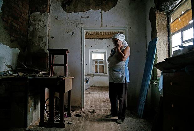 Жительница Донбасса в своем разрушенном доме