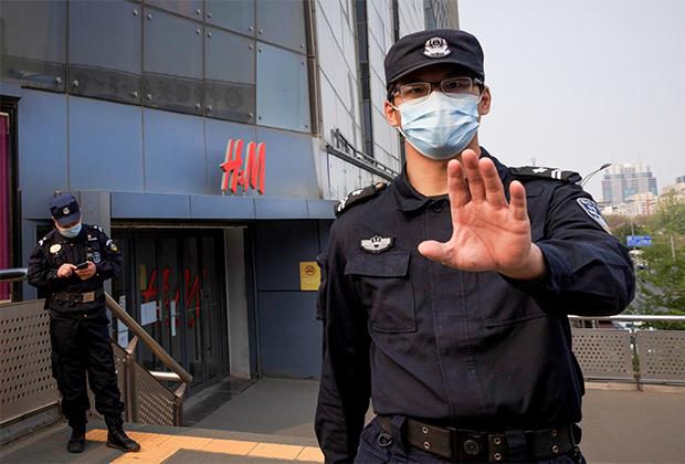 Полицейский просит не фотографировать возле магазина H&M в Пекине
