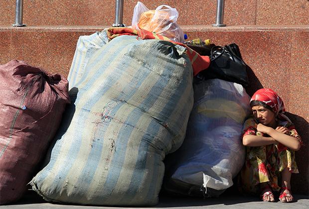 Девочка из семьи уйгуров ждет автобуса рядом с вещами в Урумчи, СУАР
