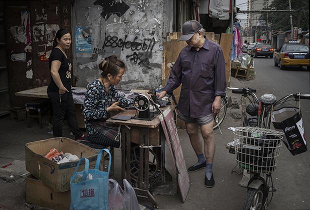 Китаец из бедного района стоит в трусах, пока портниха зашивает ему штаны, Пекин, 2015 год