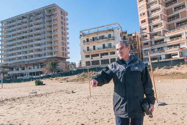 FAMAGUSTA, CYPRUS - JANUARY 05: An exiled resident visits the beach after 43 years in front of abandoned hotels Varosha quarter on January 5, 2017 in Famagusta, Cyprus. Prior to the Turkish invasion of Cyprus in 1974, the abandoned quarter of Varosha was the modern tourist area of the city, and one of the most important tourist destinations in the world.