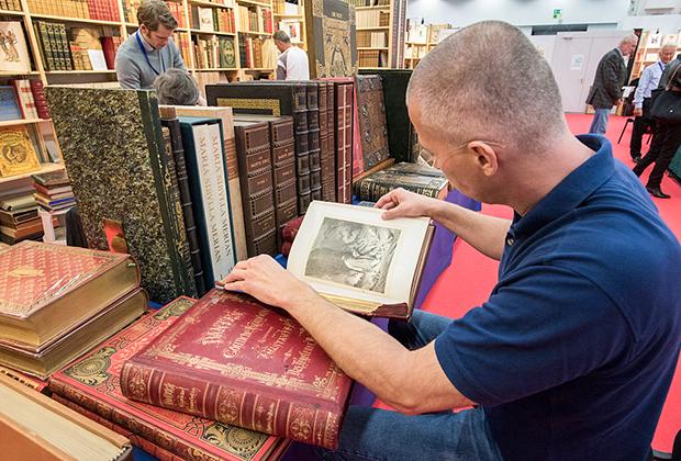 Читатель просматривает 150-летнюю «Божественную комедию» Данте