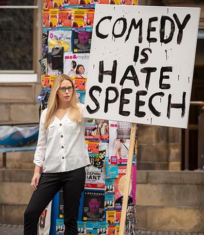 Элис Маршалл c транспарантом «Комедия— это язык вражды»