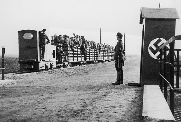 Вооруженный нацистский часовой у поезда, полного людей, на въезде в концлагерь. 1943 год