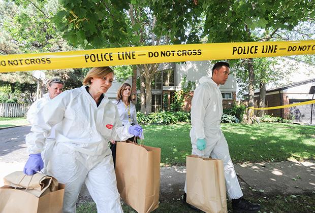 Детективы выносят пакеты с уликами из дома Харрисонов после смерти Калеба