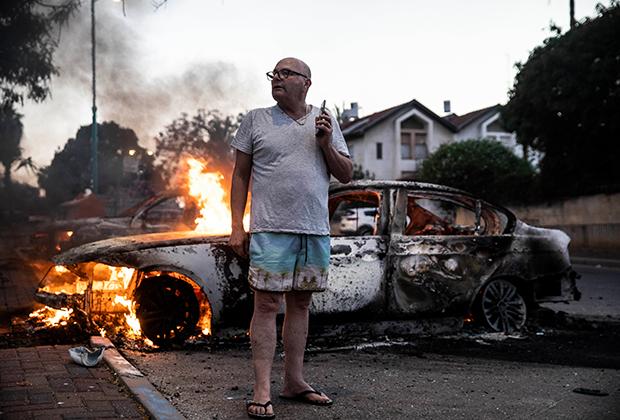 Горящая машины во время столкновений в израильском Лоде