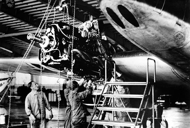 Рабочие у истребителя на заводе по производству вооружения для самолетов в фашистской Германии