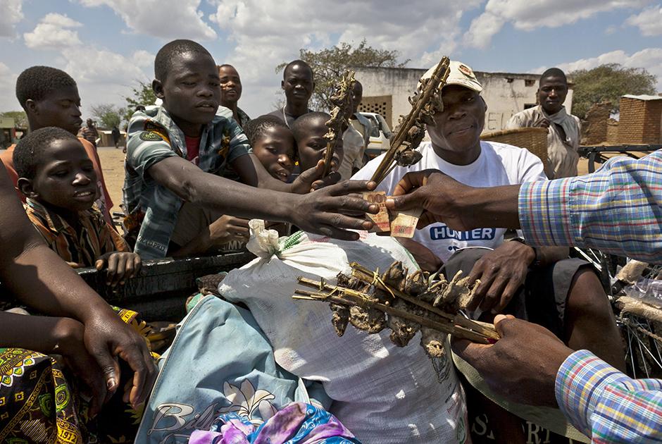 Подростки продают свой товар на дороге, проходящей через поселок Мадамба