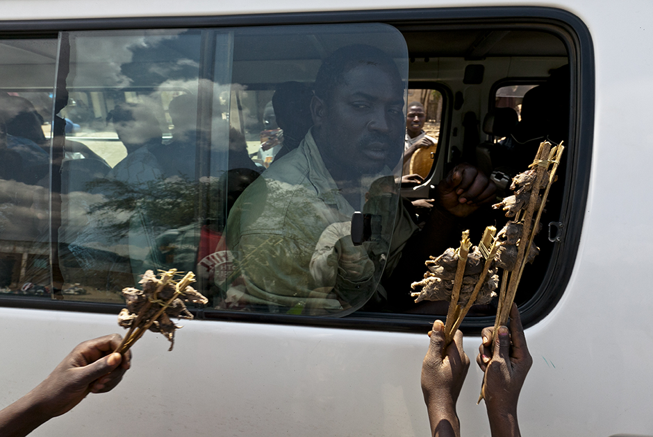 Продавцы предлагают приготовленных грызунов пассажирам микроавтобуса, направляющегося из города Тете на границу с Малави