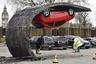 """В сотрудничестве с британской автомобильной компанией Vauxhall Чиннек в очередной раз эпатировал лондонскую публику. Он <a href=""""https://www.dezeen.com/2015/02/19/parked-car-upended-tarmac-wave-alex-chinneck-vauxhall-motors-installation-london-southbank/"""" target=""""_blank"""">создал</a> инсталляцию «Возьми себя в руки и подтянись» (Pick Yourself Up and Pull Yourself) — красную машину подвесили вверх колесами на куске вздымающегося дорожного покрытия. Часть асфальта поднимается на высоту 4,5 метра. Реализовать проект удалось с помощью спрятанных конструкций из стали, которые не дают объекту упасть. По словам скульптора, несмотря на простоту замысла большой сложностью для него была техническая составляющая. Механизм креплений Чиннек разрабатывал вместе с инженерами, специалистами по стали, плотниками, асфальтоукладчиками и малярами."""