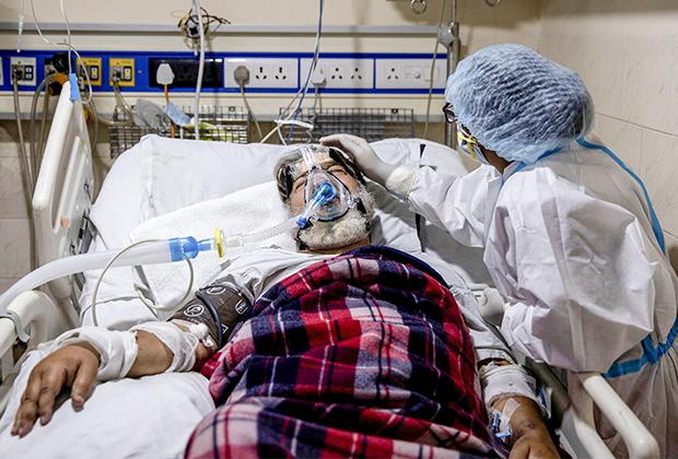 Медик ухаживает за больным COVID-19 в Нью-Дели