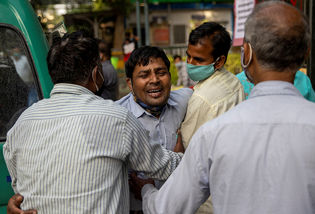 Люди оплакивают смерть родственника возле больницы в Нью-Дели