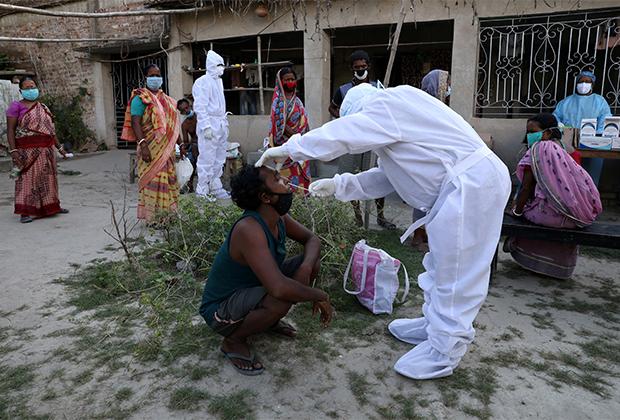 Врач берет мазок на коронавирус у деревенских жителей