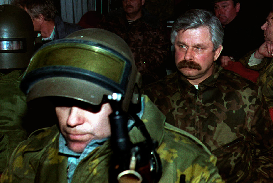 Former Vice President Alexander Rutskoi (R) sits surrounded by members of Team Alpha on a bus taking him to prison from the Parliament building October 4th after being arrested
