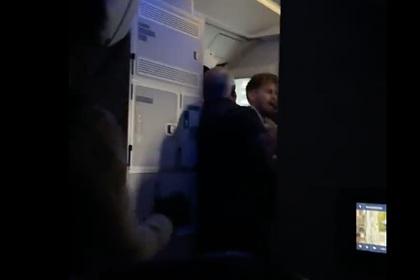 Пассажир попытался открыть дверь самолета во время полета и попал на видео