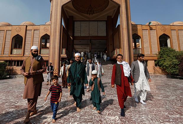 Афганские мужчины покидают мечеть после молитвы