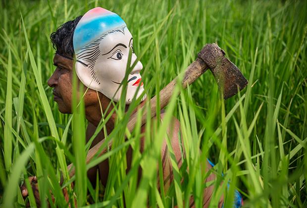 Человек с маской на затылке для защиты от тигров