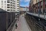 """Велосипедная дорога в финской столице протяженностью 1,3 километра была построена в 2012 году. Ее сленговое название Baana, которое переводится как «рельс», свидетельствует о транспортном прошлом — в 1894 году на ее месте <a href=""""https://www.publicspace.org/works/-/project/h241-baana-pedestrian-and-bicycle-corridor"""" target=""""_blank"""">построили</a> железнодорожный путь с тоннелем глубиной семь метров. В 2008-м инфраструктура Хельсинки изменилась, и дорога оказалась не нужна. Тогда власти решили не избавляться от объекта, а превратить его в «пространство для велосипедистов и пешеходов». В разработке проекта принимали участие местные жители и студенты-архитекторы.<br><br>За три года на трассе нанесли разметку и оборудовали инфраструктуру для комфортного отдыха: вдоль веломаршрута разместили спортивные корты, места для отдыха со скамейками, фонари и площадки для игры в пинг-понг и петанк. Разработчики сохранили природу места, <a href=""""http://www.morethangreen.es/en/baana-pedestrian-and-bicycle-corridor-in-helsink/"""" target=""""_blank"""">добавив</a> к дикорастущим растениями лианы и различные кустарники. Велодорожка быстро обрела популярность — каждый год по ней стали <a href=""""https://www.hel.fi/helsinki/fi/kartat-ja-liikenne/pyoraily-ja-kavely/pyorareitit/baanat"""" target=""""_blank"""">проезжать</a> около 700 тысяч велосипедистов."""