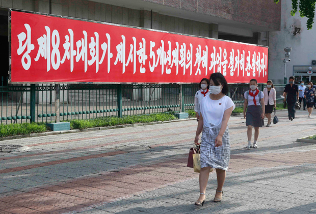 Пхеньян. Люди гуляют возле баннера с надписью «Давайте качественно выполним первые задачи пятилетки».