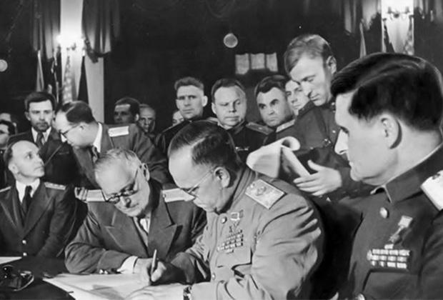 8 мая 1945 года. Карлсхорст, Берлин. Маршал Георгий Жуков подписывает Акт о капитуляции Германии. За спиной Жукова стоит полковник НКВД Александр Коротков