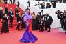 Жена французского актера Венсана Касселя, 24-летняя Тина Кунаки, выбрала для фестиваля фиолетовое многослойное платье в пол с капюшоном из коллекции итальянского модного дома Valentino. Яркая деталь в образе модели — красный бант, повязанный на талии.