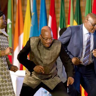 Президент ЮАР Джейкоб Зума (в центре) и премьер-министр провинции Гаутенга Дэвид Махура (справа) танцуют во время празднования Дня Африки 24 мая 2015 года в Претории