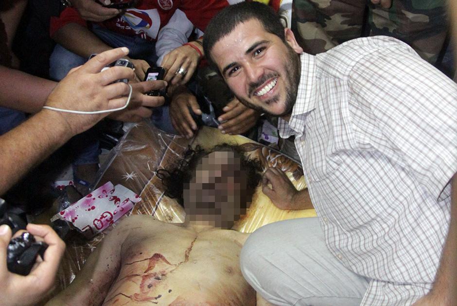 20 октября 2011 года жители Ливии растерзали своего правителя, полковника Муаммара Каддафи. Этому событию предшествовали крупные народные волнения, охватившие и другие страны Ближнего Востока, которые называют «арабской весной».   Гражданская война в Ливии началась в феврале 2011-го. Противники Каддафи обвиняли его в организации убийств и задержаний в ходе массовых протестов. Через месяц в конфликт вмешались страны НАТО, поддержав мятежников. Ливийские СМИ писали, что без западной интервенции Каддафи удалось бы подавить восстание.   Утром 20 октября авиация НАТО нанесла удары по автомобилям армии Каддафи в городе Сирт. Повстанцам удалось перехватить машину раненого правителя. Люди с криками «Аллаху акбар!» принялись стрелять в воздух и тыкать в полковника автоматами. Точные обстоятельства его гибели неизвестны, но кадры из Сирта указывают на то, что Каддафи убили сограждане: над ним просто устроили самосуд.   Смерть Каддафи — одно из самых противоречивых событий «арабской весны». С одной стороны, многие ливийцы и иностранные политики не скрывали своего удовольствия от произошедшего. С другой — гибель Каддафи не смогла остановить локомотив арабской революции. Ряд политиков и экспертов указывали на то, что такое жестокое убийство весьма далеко от демократических ценностей, за которые боролись ливийцы. «Когда на экранах всего мира показали, как его убивают, всего в крови... Вот это демократия?» — высказался о тех событиях российский бывший в то время премьер-министром Владимир Путин.