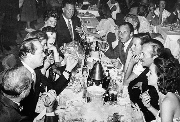 За столом слева направо: Хамфри Богарт, продюсер Сид Люфт, Лорен Бэколл, Джуди Гарленд, Элли Грем, агент Джек Энтрэттер, Майкл Романофф, Фрэнк Синатра, Глория Романофф, актер Дэвид Нивен, Йордис Генберг.