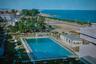 """В лучшие времена отеля его особенностью служил олимпийский бассейн, изображенный на открытке из книжной лавки Лиссабона. Надпись на обратной стороне гласит: «Это самый большой бассейн в самом большом отеле в Мозамбике. 2-я столица Мозамбика, Бейра». Оттуда отдыхающим <a href=""""http://robertcruiming.nl/grandehotel/history.htm"""" target=""""_blank"""">открывался</a> вид на Индийский океан, реку Бузи и гавань Бейры. Атмосферы добавляли пляжные зонтики и круглые столы, за которыми можно было выпить коктейль из соседнего бара. Однако плавать в бассейне разрешалось не всем — по расистским канонам, им могли воспользоваться только белые жители."""