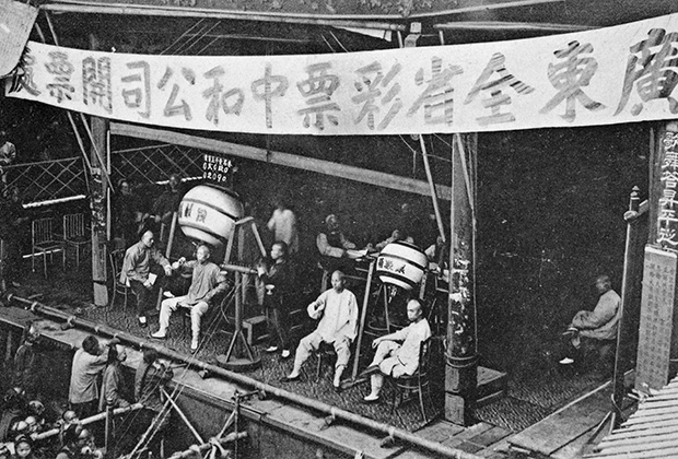Engraved postcard of a group of men sitting on a stage drawing lottery numbers from raffle drums, with the lottery players looking on, Canton, also known as Guangzhou, Guangdong province, China, published by M. Sternberg, 1910. From the New York Public Library. (Photo by Smith Collection/Gado/Getty Images)