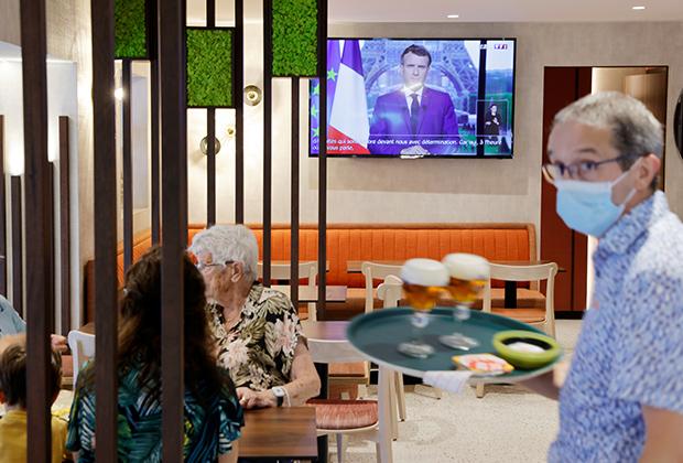 Официант подает пиво в пабе, когда президент Франции Эммануэль Макрон обращается к нации с сообщением о новой вспышке коронавируса. Камбре, 12 июля 2021 года