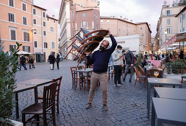 Владелец кафе собирает стулья в последний день работы ресторанов и баров перед введением более строгих ограничений против коронавируса в Риме, 14 марта 2021 года
