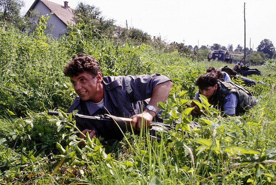 Хорватские полицейские укрываются от перестрелки в военных действиях гражданской войны, июль 1991