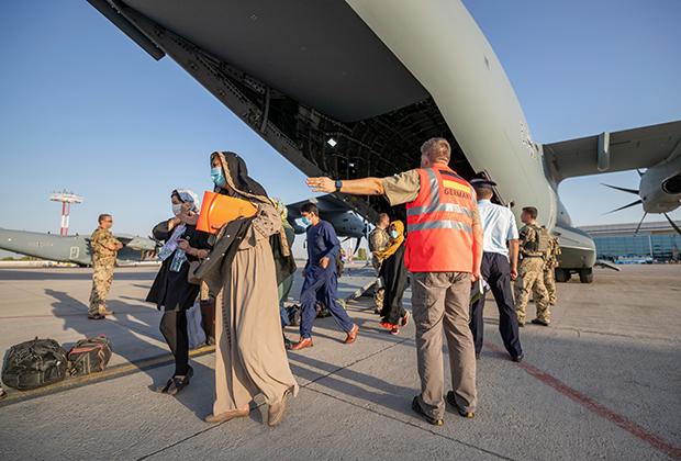Афганские беженцы выходят из самолета в аэропорту Ташкента