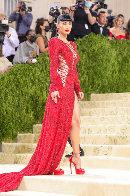 Главной темой Met Gala 2021 стала американская мода, поэтому многие гости оделись в цвета флага страны. Среди трех цветов доминировал красный, в котором и появилась на мероприятии актриса и модель Меган Фокс. Звезда прошлась по дорожке в блестящем платье бренда Dundas со шнуровкой, оголяющей ее тело, и высокими разрезами по бокам. Прическа Фокс отсылает к «Золотому веку Голливуда» — еще одной тенденции прошедшего бала.