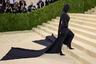 """За последние несколько дней поклонники могли забыть лицо Ким Кардашьян: папарацци <a href=""""https://lenta.ru/news/2021/09/13/mem/"""" target=""""_blank"""">засняли</a> бизнесвумен во время Недели моды вНью-Йорке в глухой кожаной балаклаве Balenciaga, что породило множество мемов в соцсетях. Таким образом она подготовила фанатов к образу на Met Gala — телезвезда предстала перед фотографами в облегающем комбинезоне той же марки с полностью закрытым лицом. Свой наряд Кардашьян дополнила почти двухметровыми волосами, собранными в высокий хвост."""
