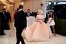 Met Gala 2021 запомнился дебютом американской певицы Билли Айлиш. 19-летняя звезда вышла на публику в пышном пудровом платье Oscar de la Renta с декольте и длинным шлейфом. Дополнив свой образ укладкой в стиле Мэрилин Монро и украшениями Cartier, исполнительница идеально соответствовала теме события.
